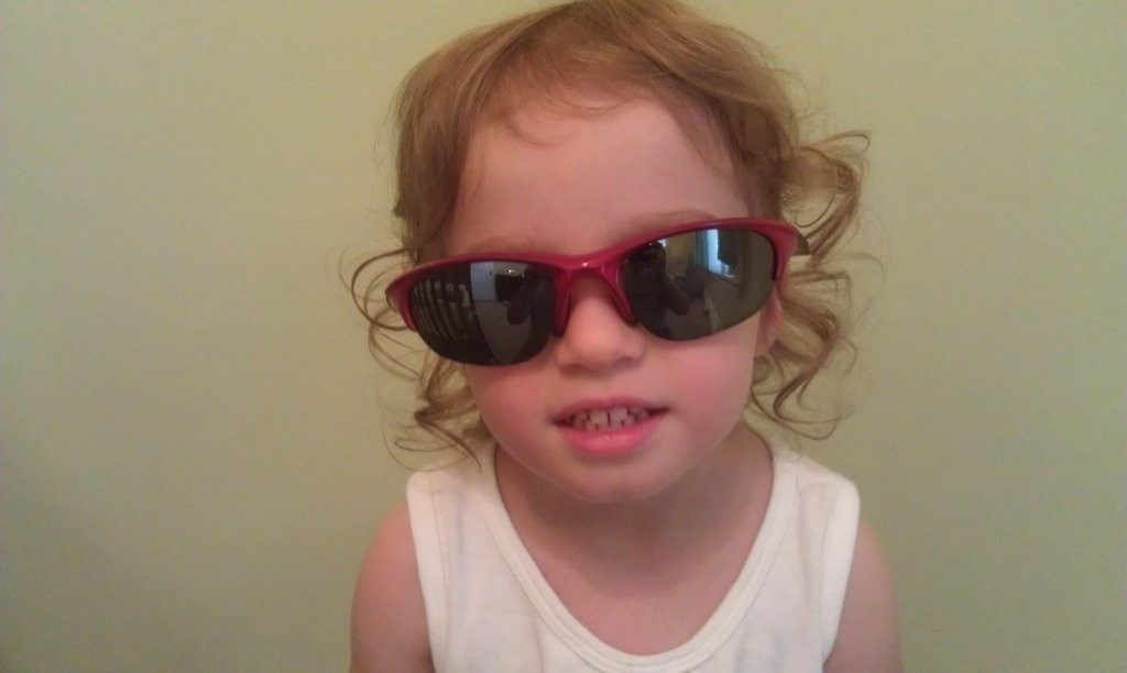 Oldest daughter with daddy's Oakleys.